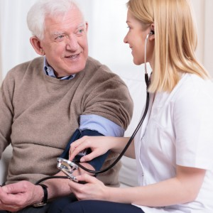 Elderly man having blood pressure checked at home